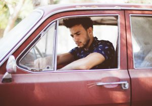 Jeune conducteur à bord de sa première voiture d'occasion rouge