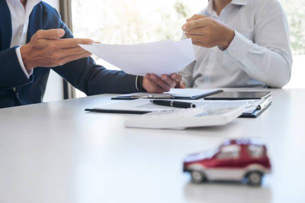 Assureur et jeune conducteur en train de signer les papiers d'assurance voiture